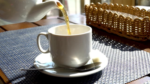 White teapot pouring tea into cup in slow motion. Cafe interior. Sunlight video