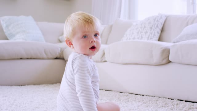 white toddler boy crawls and sits in sitting room, close up - tappeto video stock e b–roll