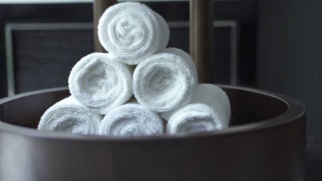 white towel roll in modern spa salon on dark background. white bath towel in dark bathroom. accessories for shower, spa sauna, swimming pool and bath - rotolo video stock e b–roll