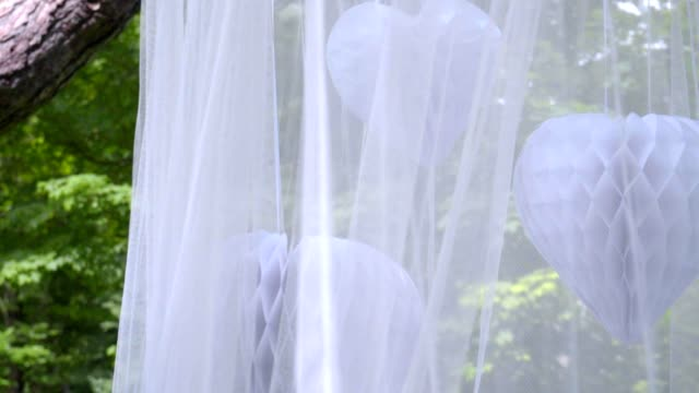 White transparent cloth on green background at park. Beautiful wedding veil video