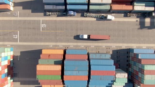 TOP DOWN: White truck transports a red freight container across the busy port. AERIAL, TOP DOWN: White truck transports a red freight container across the busy port of Los Angeles. Flying above a freight truck hauling a heavy shipment past large stacks of other containers. ports stock videos & royalty-free footage