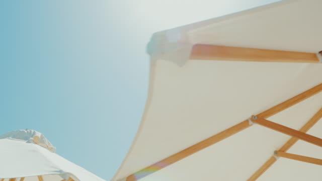 weiße schirme gegen den blauen himmel. strandurlaub im resort. steadicam-schuss - sonnenschirm stock-videos und b-roll-filmmaterial