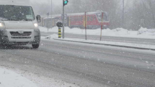 SLOW MOTION: White van drives down the slick road during an intense blizzard.