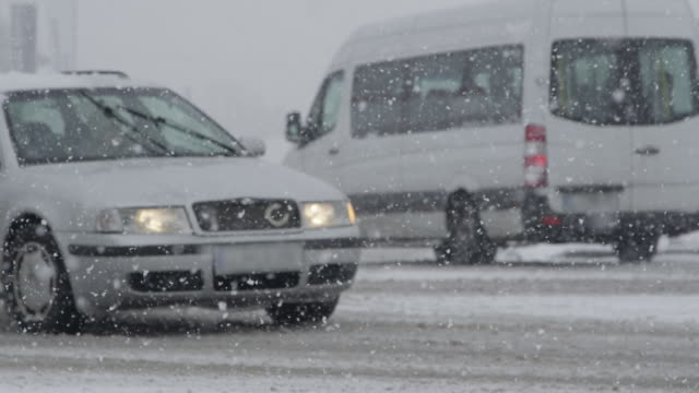 SLOW MOTION: White van steers into a side street during an intense snowstorm.