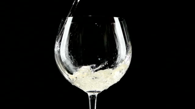 White wine being poured into a glass of black background. video