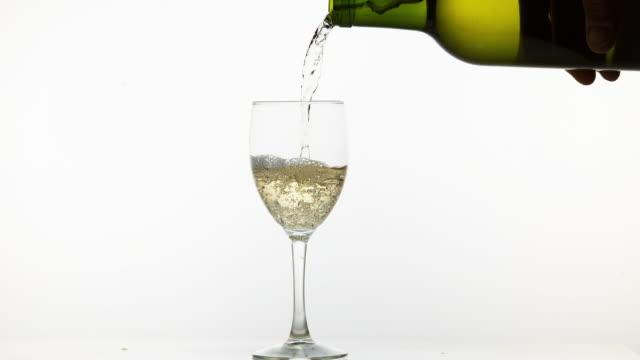 vitt vin som hälls i glas, mot vit bakgrund, slow motion 4k - vitt vin glas bildbanksvideor och videomaterial från bakom kulisserna