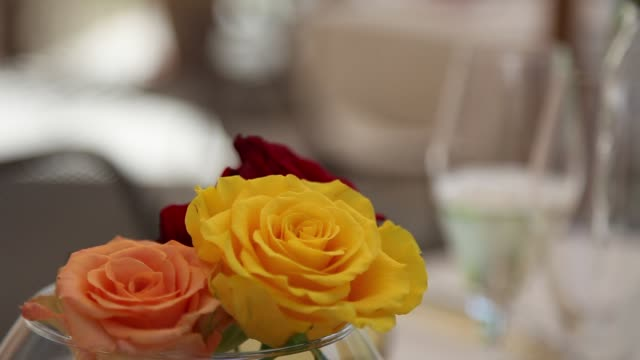 white wine poured into the flutes, and flowers on the table - video