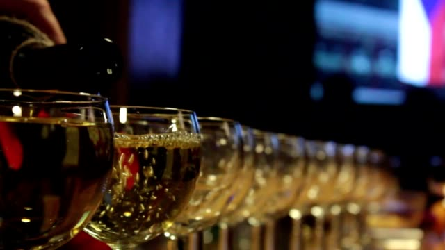 White wine pouring in many glasses. video
