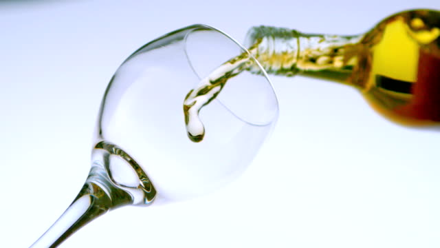 white wine pouring into a glass low angle view - vitt vin glas bildbanksvideor och videomaterial från bakom kulisserna