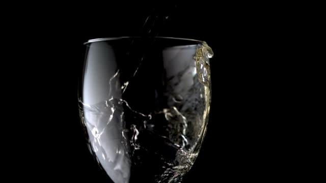 white wine pouring into glass - vitt vin glas bildbanksvideor och videomaterial från bakom kulisserna