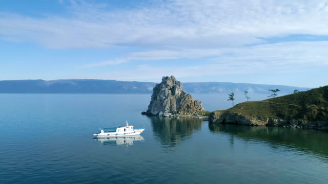 vídeos de stock e filmes b-roll de white yacht in lake cove.  olkhon island, baikal. aerial view. - lago baikal
