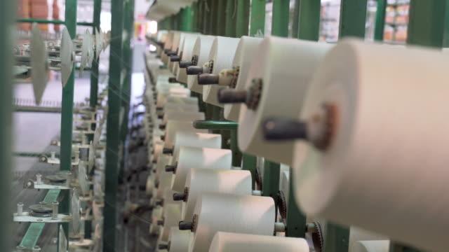 white yarn spools in warping creel of industrial warping machine in textile factory - sztuka i rzemiosło wytworzony przedmiot filmów i materiałów b-roll