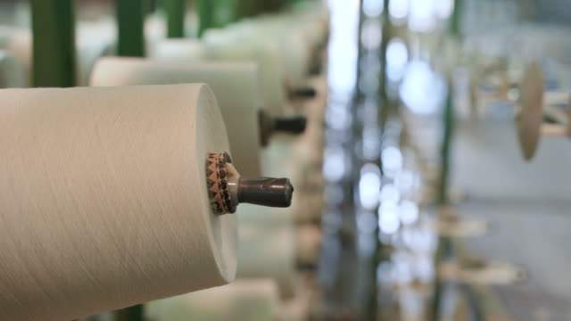 white yarn spools in warping creel of industrial warping machine in textile factory - industria tessile video stock e b–roll