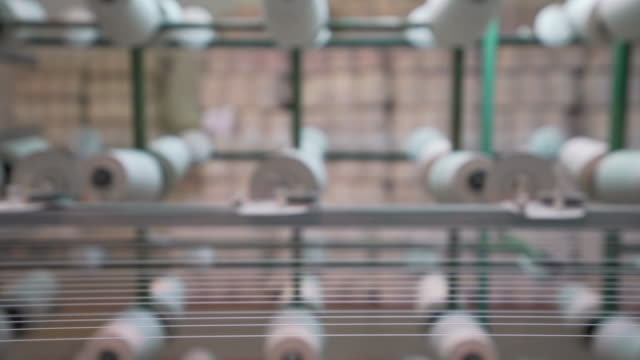 white yarn spools in warping creel of industrial warping machine in textile factory - tailor working video stock e b–roll