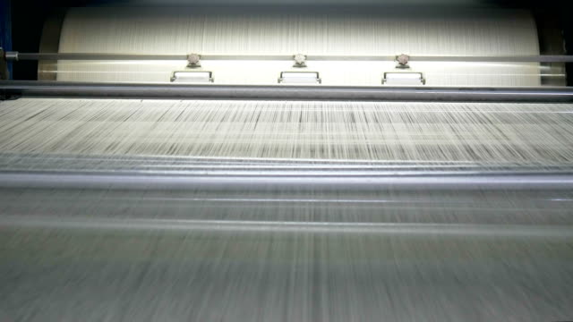 vidéos et rushes de des bobines de fil écru de machine industrielle de déformation dans l'usine de textile - fibre