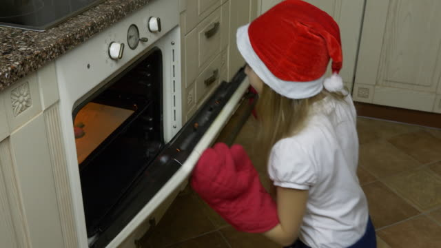 White young girl in red hat come to kitchen and looking to oven, There cookiew is ready. Girl open oven and take cookies with red mitten gloves. She smile and happy. Ready to Christmas. video