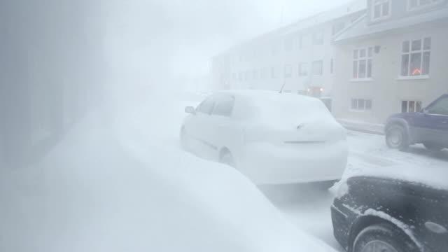 Whiteout blizzard snowdrifts blocking sidewalk cars in residential neighborhood, Reykjavik, Iceland video