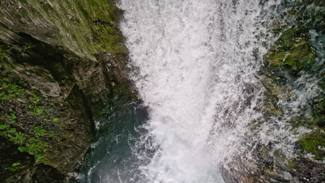 slo mo whitewater flowing over the rugged rocks creating a waterfall - muschio flora video stock e b–roll