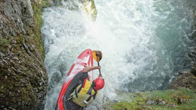 slo mo whitewater kayaker in a red kayak dropping a waterfall - rischio video stock e b–roll