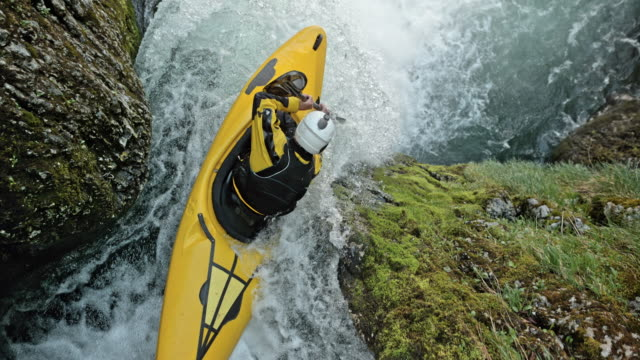 SLO MO Whitewater kayaker in a yellow kayak dropping a waterfall Slow motion wide cable camera shot above a rider in a yellow whitewater kayak running down a waterfall. Shot in Slovenia. yellow stock videos & royalty-free footage