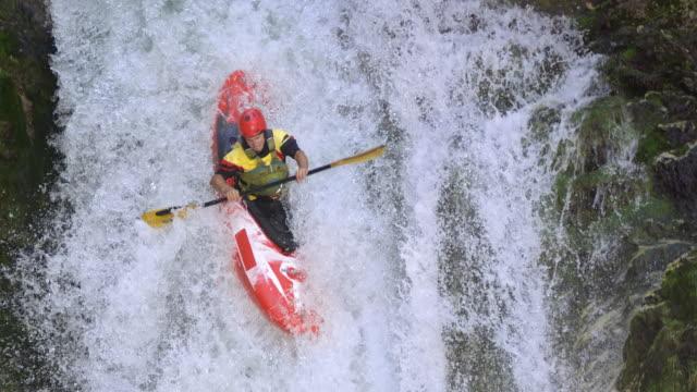 SLO MO Whitewater kayakiste fonctionnant en bas de la cascade et en appuyant sur la piscine - Vidéo