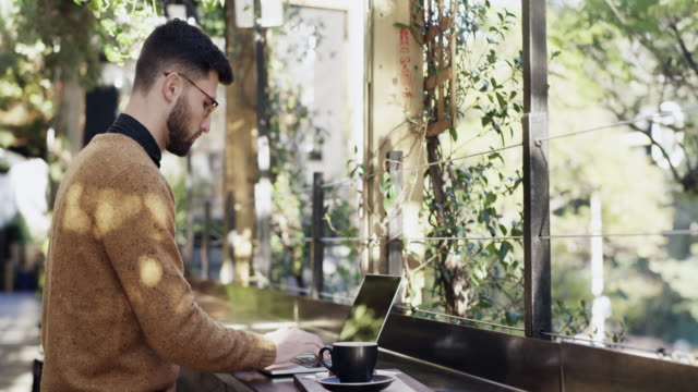Who needs an office when you've got cafes like these? 4k video footage of a young man using his laptop at a cafe coffee shop stock videos & royalty-free footage