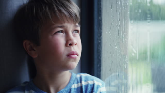 Who turned off the sunshine? 4k video footage of a sad young boy watching the rain through a window at home one boy only stock videos & royalty-free footage