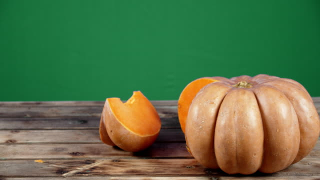 Whole and a piece of fresh pumpkin on wooden table.