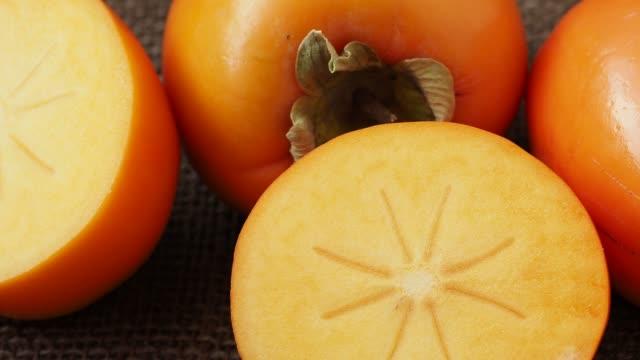 vídeos de stock e filmes b-roll de whole and half of fresh ripe persimmons. japanese persimmon (diospyros kaki) - diospiro