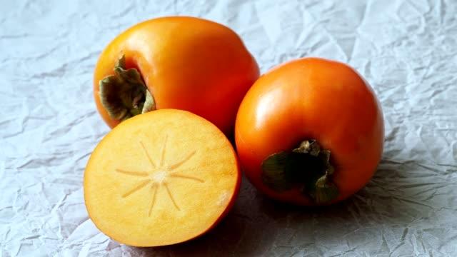 vídeos de stock e filmes b-roll de whole and half of fresh ripe persimmons, kaki fruit. japanese persimmon (diospyros kaki) - diospiro