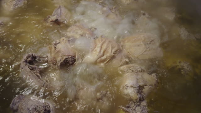 vídeos de stock e filmes b-roll de whole chickens boiled in water in a large pot in a commercial kitchen - meat texture