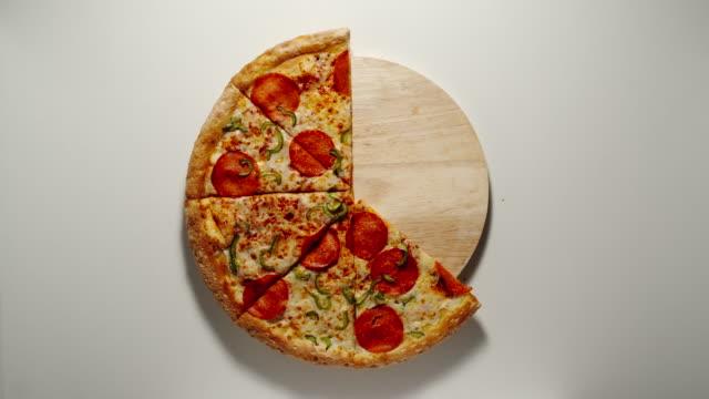 vídeos de stock, filmes e b-roll de sentido horário: o círculo inteiro da pizza grande é comido acima na placa de madeira, fundo branco - um único objeto