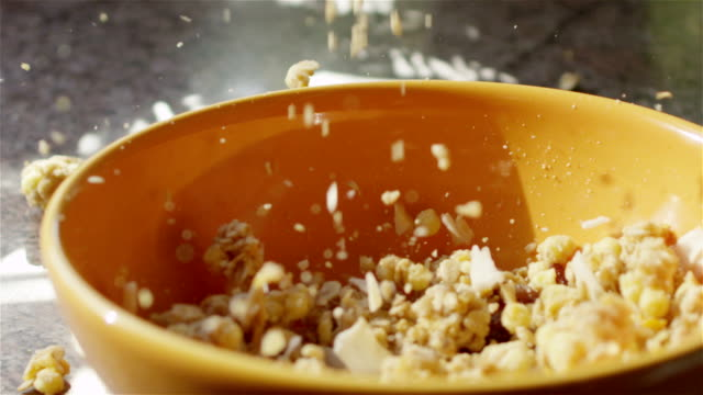 CLOSE UP: Whole grain cereal falling into bowl for breakfast video