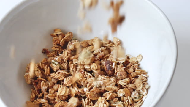 vídeos de stock e filmes b-roll de whole grains cornflakes cereal falling down on white bowl, slow motion. - granola