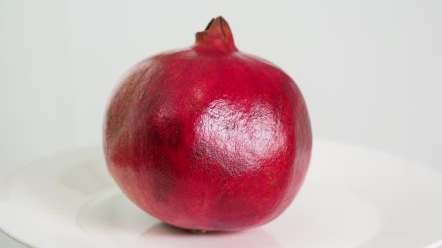 vídeos de stock e filmes b-roll de whole ripe red pomegranate fruit on white plate rotates - romã