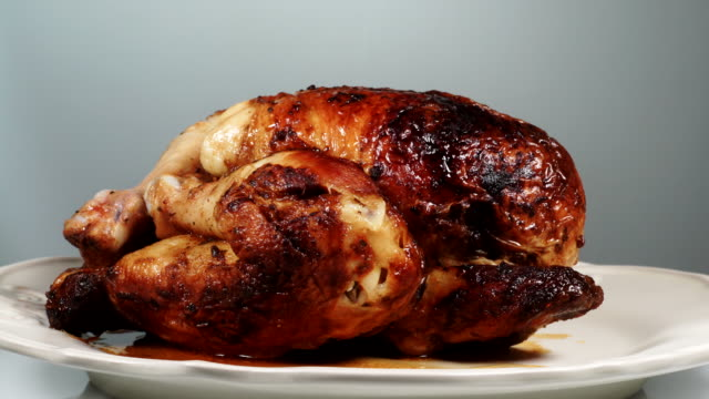 vídeos de stock e filmes b-roll de whole roasted chicken on plate - inteiro