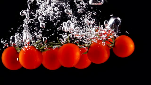 Whole Tomatoes Falling Through Water. video