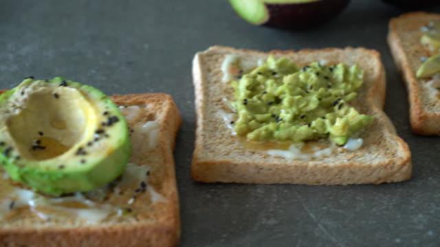 stockvideo's en b-roll-footage met volkoren brood toast met avocado - geroosterd brood