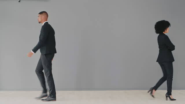 Who's side are you on? 4k video footage of young businessman and businesswoman walking away from each other against a grey studio background back to back stock videos & royalty-free footage