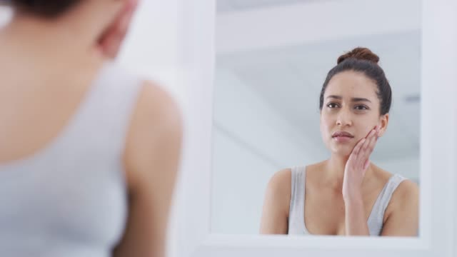 why does my skin keep flaring up? - woman mirror video stock e b–roll