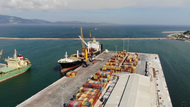 Wide aerial of container ship loading at pier.