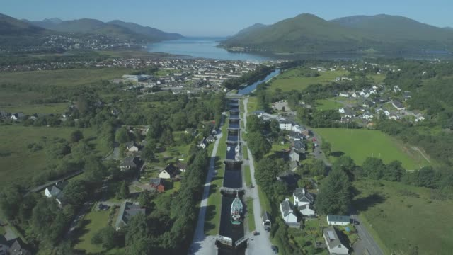 wide aerial travelling down the neptune's staircase series of locks on the caledonian canal in banavie towards loch eil, fort william, scotland - fort william video stock e b–roll