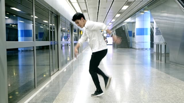 Wide angle of young man doing freestyle street dancing in underground station. Asian man.