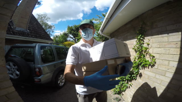 vídeos de stock e filmes b-roll de wide angle point of view shot of a delivery man arriving at a house.he rings the door bell and waits. - cardboard box