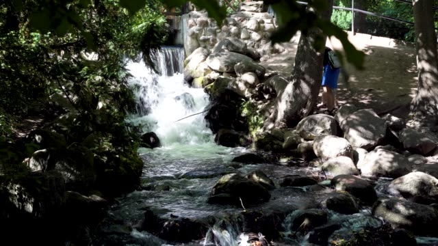 Wide angle shot of a woman and a child visiting an artificial man-made waterfall located in Park oliwski