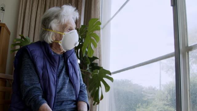 窓の外を見る取り乱した高齢の白人女性の広角ショットは、寒さとインフルエンザの季節にcovid sars ncov 19コロナウイルス豚インフルエンザh7n9インフルエンザの病気の広がりを防ぐためにn95保 - 老人ホーム点の映像素材/bロール