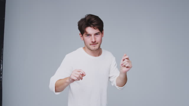 wide angle studio shot of young man against white background dancing in slow motion - kolor tła filmów i materiałów b-roll
