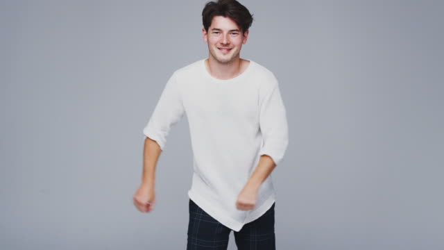 wide angle studio shot of young man against white background dancing and flossing in slow motion - kolor tła filmów i materiałów b-roll