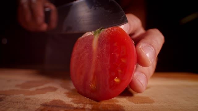 ampio scatto illuminato professionalmente di un pomodoro tagliato con una lente macro grandangolare - fetta video stock e b–roll