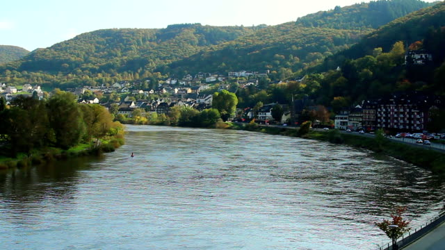 Wide river turn small village, car traffic town quay, daytime. Beautiful shot of Europe, culture and landscapes. Traveling sightseeing, tourist views landmarks of Germany. World travel, west European trip cityscape, outdoor shot video